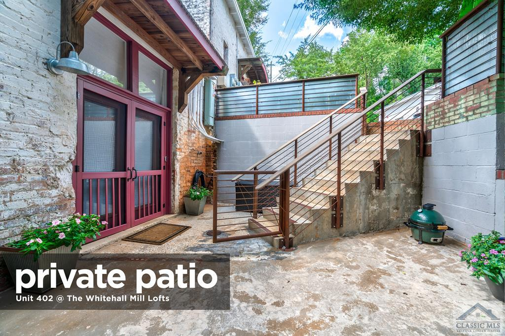 With high ceilings, a complete renovation, multiple skylights, a spacious, private patio, exposed brick and beams, you will not want to pass up this outstanding opportunity to live in this premier textile mill loft conversion - Whitehall Mill Lofts. Unit 402 is tucked away from the world, comprising the rear corner of Building Four. Enjoy the sound of the Oconee River from the private patio with gazebo that is surrounded by custom ironwork railing and a canopy of trees. A double front door leads to the open concept greatroom which includes a living area with gas log fireplace, sizable dining area, and a fully renovated kitchen. Natural, exposed beams are complemented by multiple skylights in the greatroom and by individual skylights in each of the suite-style bedrooms. High-end, stainless steel appliances including gas stove/range will delight any chef. Sizable, custom island is perfect for food preparation or libations while entertaining guests. Beautiful marble tile backsplash elevates the feel of the custom cabinetry with countertop lighting. Down the hallway with exposed brick walls are two bedrooms, one being the master suite at the rear of the condo. An electric fireplace and space for wall mounted television is flanked by custom built-ins that were expertly designed for clothing storage and can be hidden by sliding barn doors if desired. Ensuite Master Bathroom features a double vanity with undermount sinks and an oversized tiled shower with frameless glass surround. In addition to the ample storage contained in the built-in shelving and drawers, there is a walk-in closet. The guest suite also features exposed beams and skylight, and it is serviced by its own ensuite bathroom. Through a thorough renovation, quality of materials and craftsmanship were considered of the utmost of importance, and it is apparent throughout this luxurious unit. Whitehall Mill Lofts is home to not only a diverse community of residents, but also an abundance of natural beauty and wi
