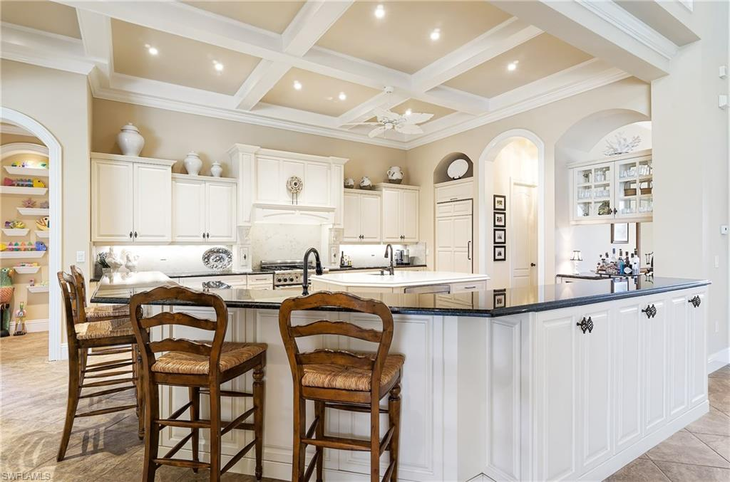 Located on one of West Bay Club's beautiful, picturesque streets this home has the greatest of great rooms. Soaring ceilings and room for all your living spaces and furniture accent this Custom home with a whole generator overlooking the West Bay Club golf course. This home overlooks the 11th hole with a sunset view and privacy beyond. A lovely yellow exterior accented with fuschia bougainvillea bushes and lush greenery truly make this a home to see. Features include two separate master bathrooms, one with a shower and one with a tub, Sub Zero refrigerator, Bosch dishwasher, steamer oven, a walk in pantry with a wine cooler, 2 en suite bedrooms upstairs with their own balcony, and a 4 plus car garages, one totally air conditioned being used as the ultimate man cave, the perfect place for your car collection or sports room to gather after golfing or a day at the club.