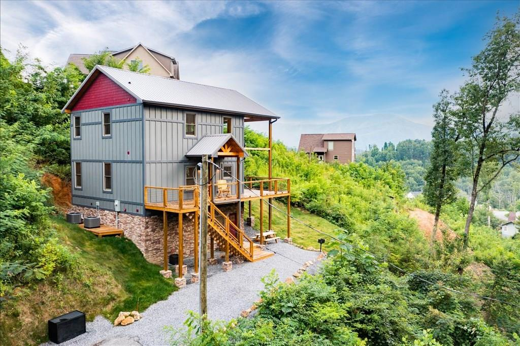 Stunning new December 2020 built cabin in the popular Chalet Village North Community! Amazing views of the Smoky Mountains, perfeclty located in Gatlinburg, with the convenience of amenities. This beautifully designed cabin is 3 levels, with 3 Bedrooms, 3 Baths, and a large 550 Sqft wrap around deck. 2 ensuite Masters with King size beds, plus an extra large bedroom on the lower level with plenty of space for pool table/game room or additional media area. Bamboo hardwood flooring throughout, barn oak laminate flooring in lower level. Remote controlled ceiling fans and LED lighting throughout. Kitchen boasts custom made hickory cabinetry, brand new stainless steel appliances with farm style stainless steel sink, chiseled black granite counter tops, and breakfast bar. Cathedral ceilings on the main level with a 2story custom stone wood burning fireplace to keep you warn on those chilly fall and winter nights. Dual Rheem heat pumps with separate w-fi thermostats. Jeld Wen aluminum clad wood frame windows. Custom log work on stairs and cat-walk. Amenities include access to 3 swimming pools, clubhouses, tennis courts, workout room, game room, and more! Perfect cabin in the Great Smoky Mountains!