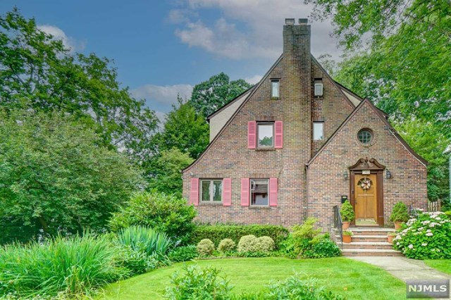 Located in the heart of Tenafly, this classic & meticulously maintained brick home is bursting w/character & curb appeal! Enter into the sunny foyer & continue on to find a traditionally elegant LR w/white-brick fireplace & elegant wooden moldings. Hardwood floors throughout, pass under the archway to reveal the classic DR which opens to a spacious office/den bathed in natural light. Enjoy preparing meals in your updated Kitchen ft/ granite countertops, SS appliances & sliding doors to the new deck. On the 2nd fl, relax in your primary BR w/ its own window seat & find 2 more well-appointed BRs for family or guests. Fully renovated Bonus Room sits nestled under a skylight on the top floor w/its own full bath! Round out your living space w/a finished Basement ft/ Laundry rm, Gym area & storage closet. Get outside and enjoy summer days on the new Trex deck overlooking the eclectic & inviting landscaping. A true gem you won't want to miss!