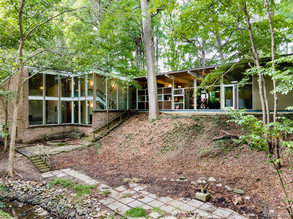 ***Highest and best offers by Saturday 9/18 at 10am.*** Tucked away in the woods , this amazing mid century modern contemporary will awe and inspire you with its unique architectural features. Enjoy nature from your elevated lookout as deer scamper by the winding creek below. Huge 2 vehicle plus car port with ample storage. Wood burning fireplace provide warmth, ambiance and atmosphere as you enjoy the view from the floor to ceiling windows. Home also has 2 ACs, 2 furnaces and 2 hot water heaters to accommodate the more than 3000 sq ft of living space. All 3 bedrooms, 1 up and 2 on the main floor, have nearby full bathrooms. Home comes with all appliances, whole house generator, built in security camera system and much more.  Must see to fully appreciate.
