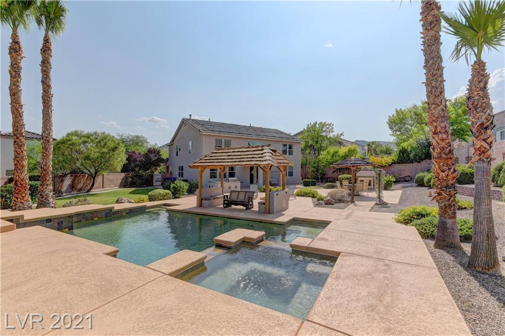 This spacious 6 bedroom, 3.5 bath home sits on an oversized cul de sac lot that backs up to Lone Mountain. This incredible backyard has a salt water pebble tec pool/spa, built in BBQ and fireplace, fruit trees, and an inground gas fire pit making this a perfect yard for outdoor entertaining. Home has 2 Primary suites, 1 being downstairs.  All bedrooms are spacious with walk-in closets and extra storage. Kitchen has granite countertops, double ovens and cook top,  stainless steel refrigerator and a large pantry. Gated community with a community park/playground. You won't want to miss this one of a kind home in this community!