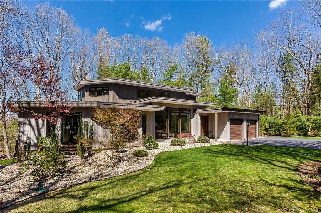 SOPHISTICATED MOD STYLE IN FABULOUS LOCATION! Ultra chic home seamlessly combines luxury & style w/innovation & on-trend design. New England transitional interweaves w/West Coast mid-century modern that takes full advantage of its surrounding landscape. Entirely rebuilt & completed in 2015 w/every inch of this over 4,000sf home outfitted w/the highest quality materials, craftsmanship, & inventive interior aesthetic. Sited at end of quiet cul-de-sac neighborhood w/sweeping driveway meandering through refined landscaping & stone walls. Open concept main level where great room, kitchen, & dining room gracefully adjoin. Soaring ceilings, a remarkable wall of windows, & dramatic built-ins set the tone for clean-lined sophistication. Brilliant hardwood floors flow throughout. Separate study offers privacy w/beautiful views. Exceptional custom gourmet kitchen w/oversized island w/leathered finish Italian marble countertop, luxury Thermador SS appliances, wine cooler, & luxe bespoke cabinetry. Incredible butler's pantry w/extensive storage, additional granite counter space, separate sink, & second dishwasher. Dining space is warm & bright w/pellet stove & large sliding doors spilling out to spacious deck just beyond for the ultimate indoor/outdoor lifestyle. Interiors open to expansive patios w/professionally designed exterior illumination. Sprawling 1st floor master bedroom suite is its own lavish oasis. Floor to ceiling windows fill the room w/abundance of light. ***CONTINUED*** Large walk-in closet, well appointed w/built-ins, along w/an additional spacious wardrobe offer optimal organization. Spa-like master bathroom is spectacular w/heated floors, a floating double sink vanity, whirlpool soaking tub, standing steam shower, separate room w/toilet, & french doors opening onto private patio. Main level is complete w/a mudroom, laundry room, & half bathroom just off attached 2-car garage & w/access to back of home. Upper level welcomes w/a lofted, open hallway overlooking great room. Additional 3 bedrooms, all w/ensuite bathroom access, provide an abundance of space for family & guests alike. Convenient 2nd floor additional laundry. The walkout lower level adds an additional approx. 1,060sf of flexible living space for a vast home gym, media room, play area, or rec room & w/a secondary home office. A plumbed & partially finished full bathroom, another laundry room, & an independent ductless heating & cooling system make basement well prepped for future expansion. With a pair of staircases, the lower level could also be imagined as an in-law apartment with its own private access. Form & function further combine with cutting edge efficiency. State-of-the-art geothermal climate control components maximize energy function & provide significant utility savings. 50-year commercial grade poured rubber roof, 4 zone sprinkler system, 400-amp electrical service, whole house humidifier, multi-zone HVAC, home audio system, & LED lighting throughout are just a few of the exceptional features unique to this property. Unparalleled in its design, this architectural gem is a must see!