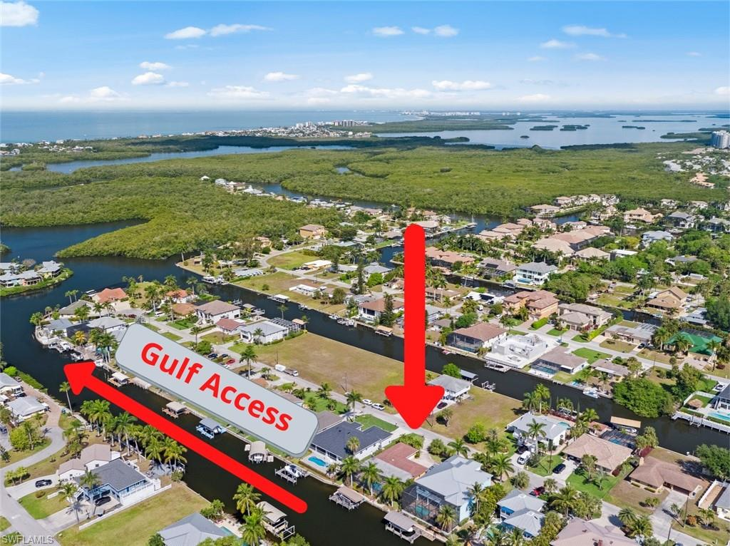 """This renovated home is a boaters paradise to enjoy all year or ideal for airBnB!  Covered boat dock with a 10,000 pound lift, complete with electricity, water, wood captains walk and located on one of the deepest canals in Imperial Shores. Also direct access to the Gulf with No bridges! In addition to boating, enjoy the paver lanai with built-in heated pool with a paver side-walk running down both sides of the home and in front of the wood boat deck. Interior has been updated with large tile throughout and hardwood in the guest bedroom.  Both bedrooms offer en-suites and sliders leading out to the lanai.  Kitchen upgrades include stainless appliance, granite counter-tops, backsplash tile. The guest bath, renovated for a king with large walk-in shower and full shower seat surrounded in tile and a """"Toto"""" commode! No cost to water your lawn as the irrigation is on a private well."""