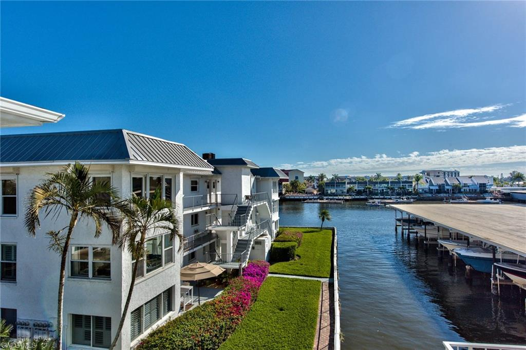 WANT IT ALL? Then this is the condo for you! Take in the water views on Naples Bay, enjoy a stroll to 5th Avenue, or take a bicycle ride to 3rd Street. Or, with your own deeded 28' boat dock right out your front door, hop on for a ride on the Bay. Not a boater, then with its 3000-pound lift, this slip can be rented for $400+/month.  This 2BR/2BA top-floor condo is in like-new condition, having been  little used since being remodeled in 2005. In addition, the A/C, refrigerator, washer and dryer are all new as of 2017. It is being offered turnkey with both bedrooms fully furnished, a breakfast settee, dining table and a comfortable furniture setup in which to enjoy the east and south southeast views. With its great location, it is still very private and quiet. The pool is across from the covered carport. The elevator is right out the front door and then directly in front of the covered parking spot.  There is ample storage in the unit, and, there is an additional enclosed storage unit near the carport.  Have it all very near downtown on Naples Bay!!