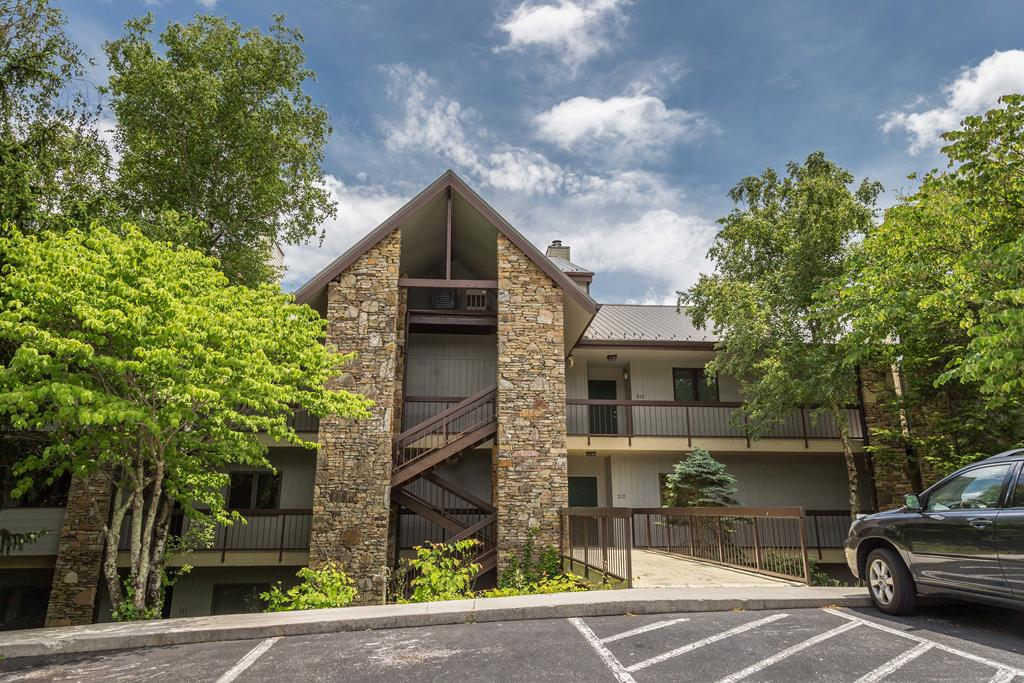 Presenting a a special opportunity to own a charming one-level condo with NATIONAL PARK VIEWS! This unit features a split-bedroom plan with a central, open living/dining/kitchen area containing beautiful newer couches, the larger one being a sleeper sofa. The spacious kitchen features loads of counter and cabinet space, and the dining room table is just a few steps away. Combined with the 4 kitchen bar stools, there is ample dining space and seating for 10!  The utility/equipment room is also off the kitchen and features a nice full-size Whirlpool washer and dryer. From the living area, you or your guests can warm yourselves by the fire, watch TV on the sizeable flat screen, or just enjoy some relaxed conversation.  Then open the door to the screened porch and soak in the mountain views.  It is the perfect place for your morning coffee and a good book. One of the queen bedrooms can open up to this porch, as well, and shares a hall bathroom with the other queen bedroom.  On the other side of the living area is the king master suite, from which you can also see the Smoky Mountains. It features a large flat-screen TV, recessed lighting over the windows, seating for 3, and two large closets in the corridor leading to the bathroom and its garden-style whirlpool tub/shower.  This unit has a newer water heater and comes with a Samsung Smart Hub system which lets you control the thermostat and and door lock remotely and includes motion detectors and other features. Outside, just two flights up, is a top-floor common area with tables and chairs facing an unbelievable, unobstructed view of Mt. Leconte and the Great Smoky Mountains National Park.  On the ground level you will find the seasonal outdoor pool and hot tub area, as well as the grilling area with picnic table, nighttime lighting, and benches facing the peaceful woods.  All this and you are only minutes from downtown Gatlinburg and a short drive to Pigeon Forge, Dollywood, and all area shopping, restaurants and attra