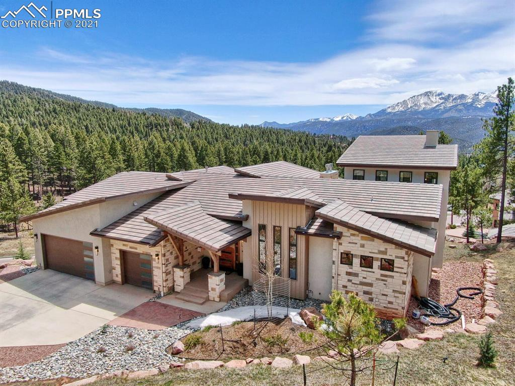 """Rustic modern luxury in the heart of beautiful Paradise of Colorado in Woodland Park with the very best views in town! Built by renowned Picasso Homes of Colorado Springs, this beautiful home has the """"best of the best"""" and endless features (too many to list here!) to please even the most particular buyer. Sitting atop a raised lot, the home has many angles and elevations creating character that entices your curiosity. Enter the main floor through the beautiful """"pivoting"""" front door where you are greeted by floor-to-ceiling windows offering the most spectacular, unobstructed views of Pikes Peak and the treed foothills from The Crags on the west slope all the way down Ute Pass to Manitou Springs! The great room has hickory flooring; high ceilings; lateral gas fireplace (total of 4 throughout the home); spacious dining room; gourmet kitchen containing onyx counters, suite of Viking stainless steel appliances and Miele Built-in Coffee Machine along with a large island offering breakfast bar seating. The main level is completed by an office space with glass mullion french doors, a lovely powder bath, and entry to the main level master suite. Again the astounding views will greet you from the wall-of-windows in the luxurious master en suite with lateral gas fireplace; 5-piece master bath and giant walk-in closet with built ins everything to include chest of drawers; and spiral staircase to the loft above with walk-out to a private deck to and even greater view! Down the wide staircase, the basement features a family room, wet bar/2nd kitchen, climate controlled wine room, theater room, powder bath, 3rd en suite bedroom with adjoining full bath, and 2nd master en suite with adjoining bath featuring double sinks, large shower and walk-in closet. Living, dining, main level master en suite, loft, family room, 3rd bedroom and 2nd master suite all have walk-out sliders to deck or patio living spaces. Schedule your own private showing to enjoy the unmatched luxurious living!en"""