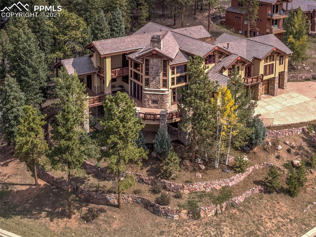 """Magnificent!  Few homes in the Pikes Peak Region can make this claim with the awards to prove it.  Winner of the 2004 MAME Award for Best Home in Pikes Peak Region, Colorado Springs Parade of Homes.   With views of Pikes Peak and the City of Woodland Park to the smallest details, this lodge-style home was dubbed """"The West"""" and will make a statement for the new owner.  This home incorporates quality with tasteful finishes of warm woods, natural stone, Saltillo tile, granite, and copper.  Located within the upscale Paradise Estates in Woodland Park; this home is near permanent access into the National Forest yet is just minutes from downtown.  Additional features include an elevator to all home levels, heated three-car garage, and a kitchen with everything the chef will appreciate for a wonderful dinner presentation.  Wine bar at the dining area is great for entertaining.  The great room is massive yet has a warm feel for conversation with a gas fireplace and massive rock front as the center of attention.  The master bedroom suite is complete with its own laundry, walk-in shower and dual-facing vanities for the owners, and separate closets for each season!  The guest level includes accommodation for your pool table or sports screen and two bedrooms complete with each its own laundry.  The lower level is where family and guest entertainment thrives!  A dedicated space for cards, gaming or reading, a home theatre with rear projection capability, a well-appointed wet bar, and a spacious relaxation area around this level's fireplace.  The lower level also includes a fifth bedroom ideal for accommodating long-term guest or family member.  Plenty of exposed and covered decks on three sides of the home. The outdoor gas fireplace on the main deck area is located ideally for outdoor conversations on those chilly nights.  See this home now, it's guaranteed to make your heart beat faster!"""