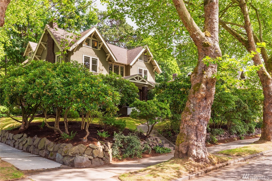 Classic 1909 Grand Craftsman perfectly sited on a lg corner lot (10,000 SF). Your back yard is Volunteer Park & your front is Federal Ave E, one of Seattle's most sought after streets. Gracious formal rooms w/beautiful detailing, 3 fireplaces, a library, office, 3rd floor loft studio w/bdrm & bath plus separate apartment. Sun filled cook's kitchen opens to south-facing deck & yard. Covered front porch w/an original porte cochere, plus parking for 3 cars in back. Garage converted to studio/apt.
