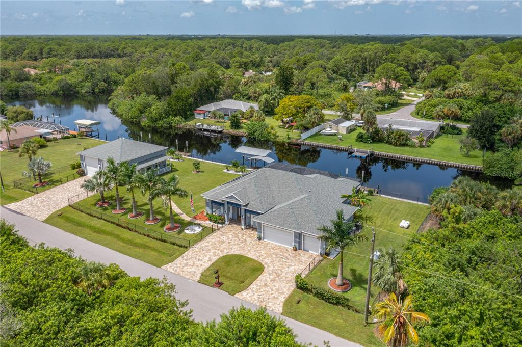 FEATURED HOME ON TV! Out And About SW Florida on Fox4 September 26, 2021. Bring ALL of your toys to this one! This Gulf access home (10 minutes to open water) sits on 3 lots with an amazing 240 feet of waterfront. Not one, not two but, 3 docks! One dock is covered and the 10k lb. boat lift is covered! Electric and water are at main dock. If your attached oversized 3 car garage with luxury roll down screens isn't big enough, your 40x40 detached garage on a 6 inch concrete slab with 2 RV doors (16 ft ceiling) will be! Detached garage is set up with 240 volt, 50Amp electric source to plug in! You won't be able to fill this up! Both garages have beautiful epoxy floors and wall a/c units! Whole house AUTOMATIC generator runs on propane and has a transferrable 5 year warranty! The entire home has 12 foot ceilings and 9 foot solid wooden doors. Walk through your double door entryway with stained glass and see an open floor plan with a view of your beautiful remote controlled salt water heated pool and the Cheshire Waterway. Zero corner sliding doors offer non stop views. The screened-in lanai has so much room for lounging and dining and has the luxurious detail of a cedar wood ceiling.  The custom pool has 2 waterfalls, LED lighting and a Baja shelf for relaxing.  In the masterful kitchen, you'll notice the sub zero refrigerator/ freezer (5 ft. wide) and the stylish real wood cabinetry with soft close doors and drawers. You will also notice the higher end veined granite countertops that span across the surfaces and the custom lighting.  The built-in oven is convection and all appliances are stainless.  A walk-in pantry has beautiful custom doors with glass design. The master suite includes a bedroom with 2 sliding doors that offer incredible views and access to the pool, a master bath with separated vanities, clawfoot tub, walk-through Roman shower, and a California closet measuring 14x8. The master closet also has another door that accesses the laundry room! Tile flooring