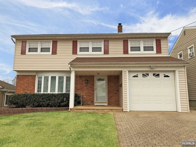 Deceptively large 4/5 BR & 2.5 bath Colonial with 2,123 sq ft of living space! Plus a huge basement that can easily be finished for Rec Rm/Play Rm/Gym & more! Updated & move-in-ready! 1st flr features entry foyer, living rm w/hardwood flrs & dentil crown moldings & a beautiful Castle Bay Window, dining rm, updated eat-in kitchen w/granite counters, half bath, & a bonus rm w/sliding glass drs to the yard for den/office or even 1st flr 5th BR! 2nd flr has 4 large BRs incl 2 MBRs! One has a suite w/full bathrm, & one has 2 walk in closets (one could be used as an office or into another full bathrm!) Rear BRs have beautiful vista views of the mountains & sunsets! All this & Central AC, 2 zone heat, ample closets, 1 car garage, beautiful brick driveway, & private backyard for BBQs & gatherings for this Spring & Summer! All on a great street in desirable Wood Ridge! Minutes from shopping, dining, NYC transportation, highways, schools, and more! Dont Miss !