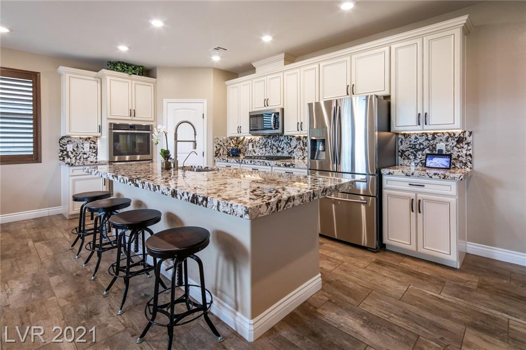 Incredible opportunity in Summerlin West's Stonebridge neighborhood.  This model-perfect POOL home has been impeccibly maintained and features all the bells and whistles.  Highly upgraded kitchen with double built-in ovens, 5 burner cook top and oversized granite island gives way to open concept family room and dining. There's also a flex room that can be used as an office, home gym, or den.  Upstairs primary retreat has a balcony with mountain views as far as the eye can see, and a spa-like bath with separate tub and shower and double sinks.  Both upstairs secondary bedrooms are oversized, and there's also a loft.  Outside is your private oasis with pool, spa, covered patio with TV hook-up, and no rear neighbors. Truly a gem in the desert!