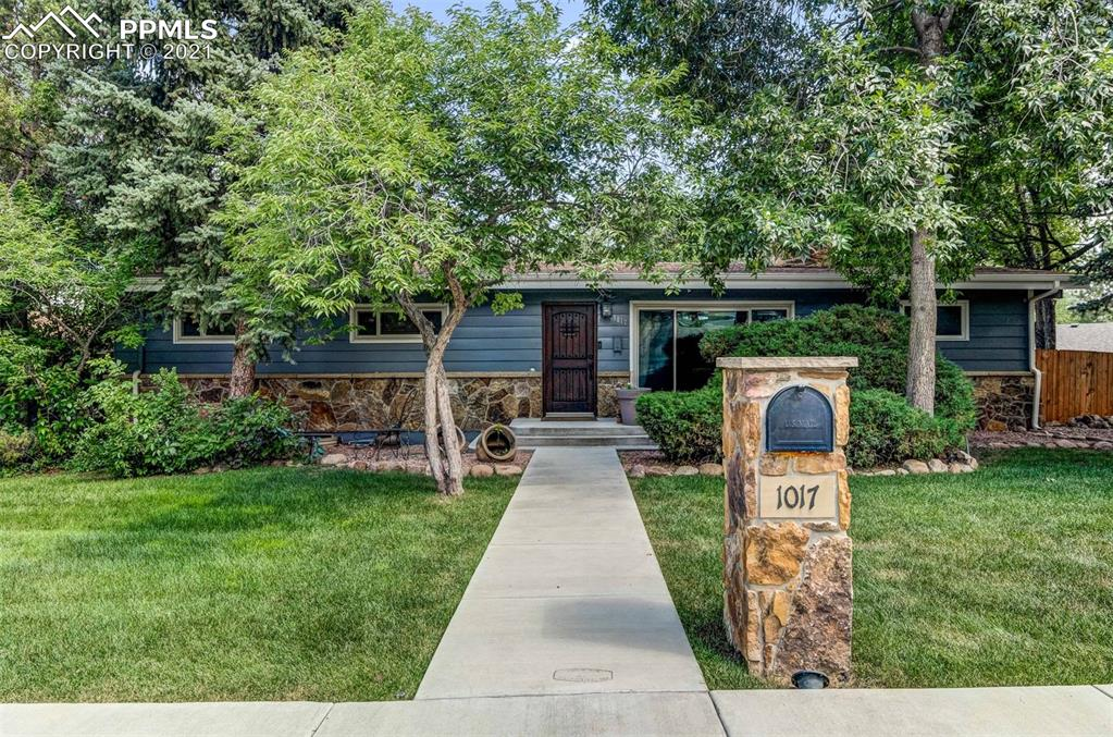"""This one-of-a-kind, ranch-style home sits on an enormous corner lot, located in the heart of Lower Skyway & School District 12. The house is directly across the street from """"The Little Dipper,"""" neighborhood swimming pool, & walking distance to Skyway Elementary School. The entire property is full of custom upgrades inside & out! The lot offers a perfect design for those who enjoy being outside & entertaining with a large outdoor living area, built-in gas fire-pit, built-in kitchen with gas grill & granite counter-tops, stamped concrete, large covered deck with hot tub, outdoor tv with tv connection ports & surround sound, 2 large storage sheds, oversized 2-car detached garage, new backyard fence, freshly poured sidewalk & curb, auto sprinkler system, healthy grass & mature trees all around. As you approach the home, you'll immediately notice the exterior stone accents (Colorado Native Moss Rock), custom-made speakeasy front door, refinished hardwood floors & stairs, fully remodeled kitchen with granite countertops & SS appliances, remodeled bathrooms, custom bookcases with secret compartments, wood shutters, beautiful wood-burning fireplaces, wine bar, reflective acrylic floors in basement, upgraded windows, new light fixtures & SO MUCH MORE. Do not miss out on this one!"""