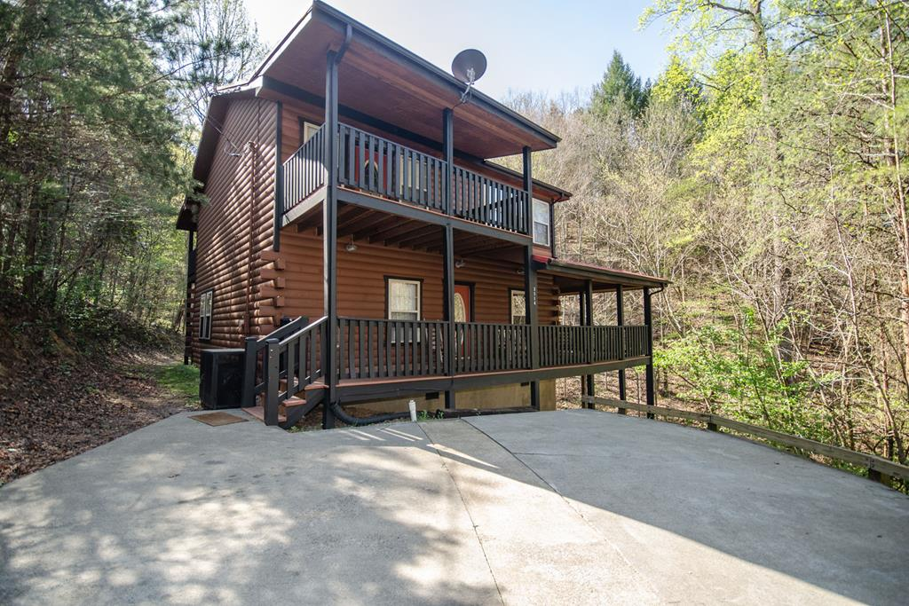 EXCELLENT LOCATION!!! Spacious 5 bedroom cabin and a creek just minutes from downtown Pigeon Forge. Motorcycle accessible with plenty of level parking. Airy living room with stacked stone fireplace, French doors leading to a huge deck with a bubbling hot tub. Fully equipped kitchen open to dinning room and living room gives you all the comforts of home. Gleaming tongue and groove, dramatic vaulted ceilings, windows throughout. 2 bedrooms on the main level. Huge master suite upstairs with a jetted whirlpool tub and private bathroom. Large game room with pool table. Two more large bedrooms are located upstairs. Play a game of pool, take a relaxing dip in the outdoor hot tub, or take in the nature's beauty on one of the three covered decks to and listen to a babbling creek. .Recently re-stained both house and decks.  Comes fully furnished with all appliances and furniture.  Deck is wraparound on three side sides.  Sleeps 12 adults with five king beds and one sleeper couch. Pool table in recreation room on second floor and 3 hole putt-putt golf holes on back and side deck.  Already booked for $43,871 for past and future bookings for 2021.