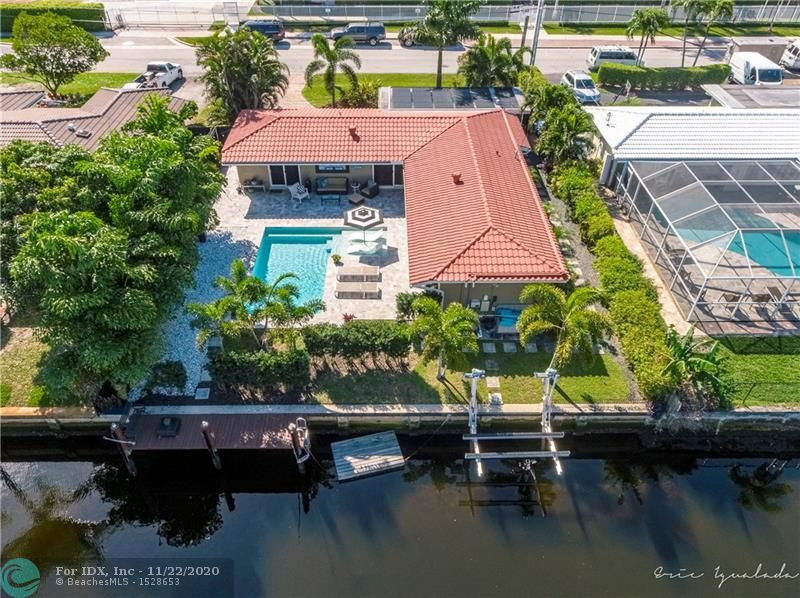 Welcome home to this fantastic waterfront, pool home. Significantly updated since 2016, this home features a stunning resort style pool with travertine pavers, salt system + solar heat. The dock and boat lift were installed in 2017 along with impact windows and doors throughout the home. There's a great flow with sliders leading to the pool from the kitchen, master, guest, and living rooms. The layout maximizes the natural light and the well planned landscaping is not only beautiful, it gives great privacy. The roof was sealed and painted, electric was upgraded, new a/c AND ducts in 2017. Natural gas from the street serves the H2O heater and dryer. Three fixed bridges to the Intracoastal, appx. 30 minutes to the inlet. Super location, close to the beach, restaurants, shopping, I95 and more
