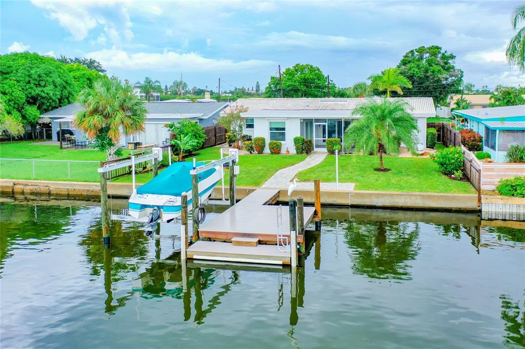 Waterfront in Indian Rocks Beach, anyone? How about 65 feet of it in a deep-water canal off the main channel of the Intracoastal waterway where dolphins play, Great Egrets make new friends, and where pelicans dive daily for dinner. This beautiful and bright split-plan block home on much-desired La Hacienda Drive represents the tradition that builder Charles Rutenberg started more than 55 years ago with meticulous craftmanship and style. But now, this home sports new PGT sliders and windows, a composite dock with water and electric, a Neptune boat lift, new flooring, paver walkways, and so much more! This house can be your new paradise, either year-round or seasonally, or it can become a lucrative investment, as short-term rentals are allowed here. The living area can be completely opened using the five pocket sliders leading to a large screened lanai, and there's no need to update landscaping, as new trees, shrubs and flowerbeds are all protected with cedar-crafted wooden privacy fencing and gates. The exterior is in excellent shape with new gutters with six-inch downspouts, new doors and painting. The over-sized garage can easily hold two cars plus plus lawn equipment, and has built-in storage. Come see this home to experience its quality, uniqueness and magical setting!