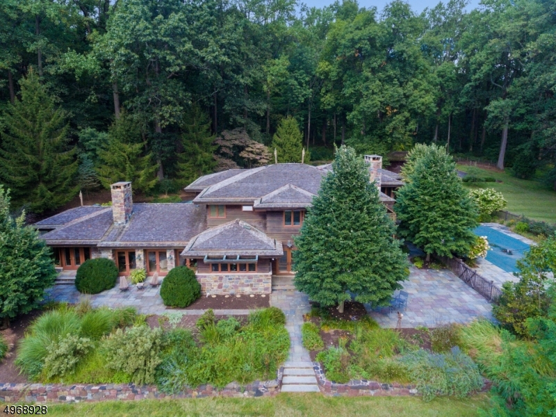 Magnificent Frank Lloyd Wright inspired 5 BR, custom home w/appx 5800sqft , 7+ serene acres. Open layout with countless upgrades & 4 Fireplaces. Low taxes & great schools in prestigious Harding Twp. Exquisite sun drenched, 5 BDRMs, 5.2 baths, Open layout with gorgeous FDR, bright EIK, w/custom cabinetry, high-end appliances & large island. The FR with floor to ceiling stone fireplace  is the perfect spot for entertaining w/ seamless transition to the Bluestone Patio and Private Pool offers a private outdoor oasis. Easy living w/4 car garage (one attached) and mudroom with access to the kitchen. W/D on 1st floor. Magnificent Master Suite Wing with fireplace & luxurious Master Bath  Full, finished basement w/gym, large rec room, Full Bath and Kitchenette complete this home. You'll never go on vacation again!