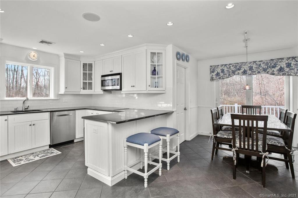 On top of the world sits this lovely contemporary home in coveted North Stamford neighborhood.  Vaulted ceilings, large rooms and seamless flow!  Lots of windows, sliders and skylights accentuate the natural light.  The updated kitchen features granite countertops, RADIANT HEATED tile flooring, a sizable pantry and a breakfast nook.  The laundry room is conveniently located just off the kitchen.  Enormous living room and family room, each with their own fireplace.  Working at home these days?  Set yourself up in the dedicated office on the main level, both private and bright.  On the second level you will find the master bedroom with stunning updated bathroom, complete with shower stall with barn slider, two separate sinks and a lovely soaking tub.  The 3 additional bedrooms share the hall updated hall bathroom with tub/shower and double sinks.  Want more space still?  The TREX deck, accessible from 3 rooms, is grand with 2 levels and is surrounded by natural wooded area that offers just the right amount of privacy.  The Hardy Board siding frees you from ever having to paint or replace the exterior siding.  Well maintained systems and a (truly) oversized garage complete the picture.  Just 5 minutes to schools, shopping and prkwy.  What more could you ask for?!