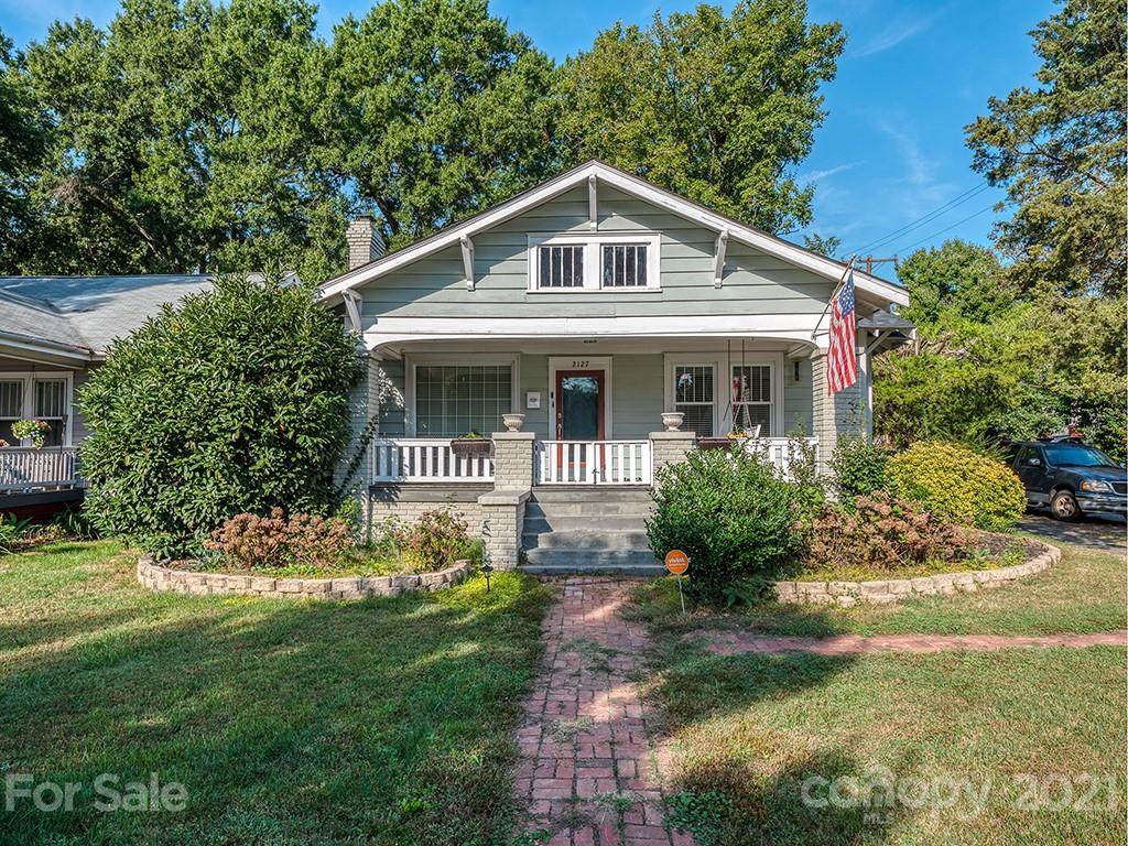 Live on the most historic street in Plaza Midwood in a quintessential bungalow situated on a corner lot. The front porch overlooks the tree-lined street and features mature landscaping. Upon entry, the freshly-finished original hardwoods and high ceilings are accented by a gorgeous fireplace. This home has a fantastic layout with the living room adjacent to the dedicated dining room which flows into the kitchen. The primary bedroom is light-filled and features a large closet. The secondary bedroom is well-sized and there are two full bathrooms. This home also features a back-entry which is the perfect flexible space for an office or whatever you need! Convenient corner location and parking is accessed via Mimosa Avenue.