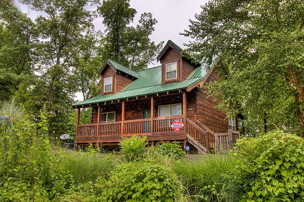 Delightful Cabin in the Heart of Pigeon Forge. This log cabin is located less than a mile off the Parkway in Pigeon Forge which makes it an ideal location for easy access to shopping, restaurants, and all of the area attractions. This spacious cabin offers three bedrooms each with a private bath (two of the bedrooms have gas log fireplaces) a large living room which opens onto the rear deck, an eat-in kitchen with an abundance of cabinetry, a spacious rec room complete with a pool table, and a cozy loft. Features include hardwood floors, whirlpool tubs, hot tub, front and rear decks, and three fireplaces. This is a great opportunity to invest in a money making vacation rental property in Pigeon Forge. The cabin is being sold fully furnished.