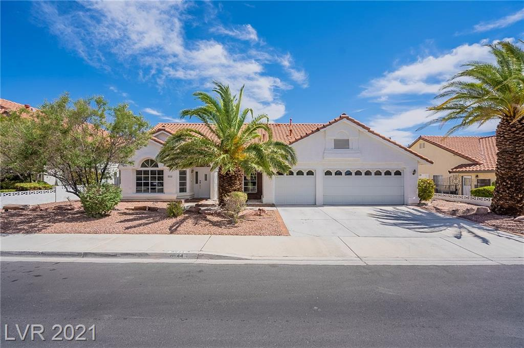 This Las Vegas one-story home offers a patio, granite countertops, and a three-car garage.