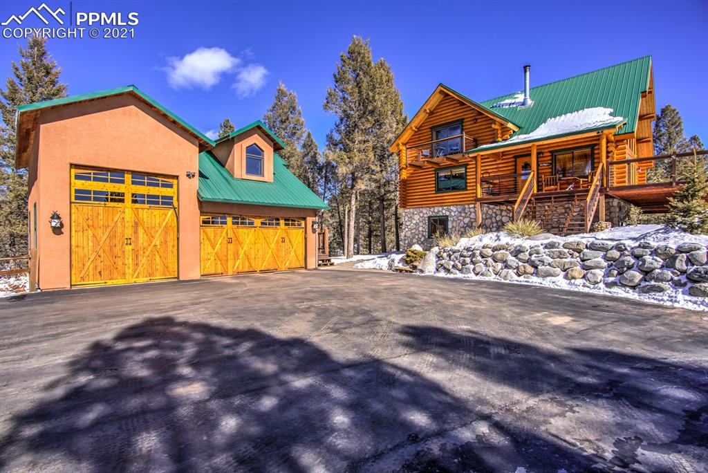 This quiet, private, picturesque Colorado Mountain Swedish Log Home is nestled among the pines with a southern exposure looking immediately into the Florissant Fossil Beds National Monument and providing sweeping views of Pikes Peak and the Wet Mountain Range! This log home offers 2 lots totaling 5.66 acres! As you approach the home you will be greeted by a paved driveway with professionally landscaped river rock and siloam stone accented entry way. The covered entryway into the great room is full of trapezoid windows allowing an abundance of natural lights and the entryway also adjoins a spacious deck which wraps around three sides of the house! The open Great Room on the main level offers soaring wood ceilings, beautiful hand pealed log timbers, wood stove, lots of natural light and spectacular views. The main floor contains a great room, open kitchen, bedroom or office, dining area, full bath and laundry room. The open kitchen comes with high-end Bosch appliances. Birch wood floors, Tongue and Groove Ceiling's, and granite counters throughout the entire home! The 2nd floor consists of a large master bedroom with vaulted ceilings, a huge walk in closet, large custom shower/bathroom and a deck to enjoy your morning coffee. The finished basement with its 9' ceilings has a game room, wet bar, full bath, bedroom and an entertainment room with a walk out basement to a patio area that is wired and ready for a hot tub!  Only steps away is a detached oversized two car plus one rv bay garage with an upstairs apartment currently being used as a workout room 640 SqFt with a bathroom and shower! The garage is large enough to park your RV or boat. The garage is large enough for the shop you have always dreamed of!  There is plenty of parking on the paved driveway pad, or if you choose there is plenty of land to build another residence or just enjoy the wildlife wonder through both parcels of property. This home has too many extras to list, don't miss out on The Colorado Dream!