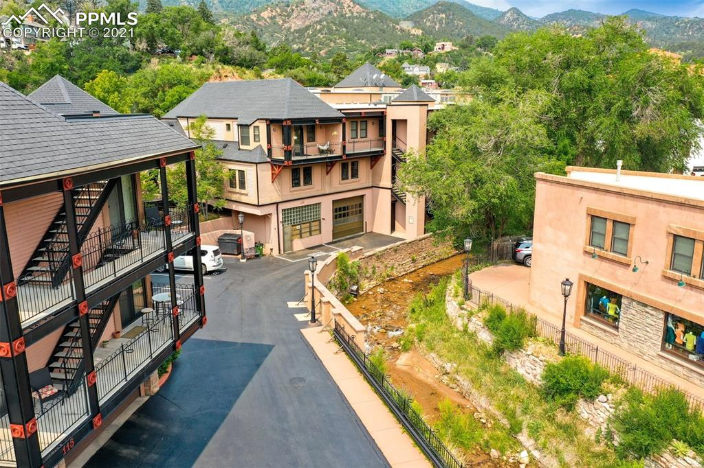 Your rare opportunity to own one of the coveted Manitou Lofts in the heart of Manitou Springs!  2 bedrooms, 3 baths, 2 car garage parking with additional 3rd parking space in private gated lot.  Constructed in 2005, the lofts and shops were developed atop the historical General Motors Pikes Peak test facility which still serves as the building's foundation.  This creekside paradise is located in the midst of the action while still maintaining a quiet and private atmosphere.  Designed as an artists' loft, this amazing home features outstandingly original touches throughout including concrete countertops, iron work by local artist Doyle Svenby, stone sink bowls, and so much more.  Featuring 17' ceilings with skylights throughout, this spacious loft offers a gourmet kitchen with Jen-air gas range, warming drawer, Jen-air fridge, and large island.  Gather around the gas fireplace in the great room or head over to the den for a cozy movie-night in.  Formal dining space overlooks all the excitement on Manitou Avenue.  Main level suite offers a large walk-in closet and stunning 15x7 4 pc private bath with double vanity and oversized glass shower w/seating.  Lofted secondary suite offers a large walk-in closet and private 3/4 bath.  *Third 3/4 bath on main level for guest use  *Central A/C  *Private creekside pavilion to host your gatherings or just enjoy the sounds of the water  *Secured street-side lobby entrance with residents' mailboxes  *Massive 17x7 storage closet in garage  *Gated Entry *Mountain Views *Downtown Views  *INTERACTIVE VIRTUAL TOUR LINKED IN MLS*