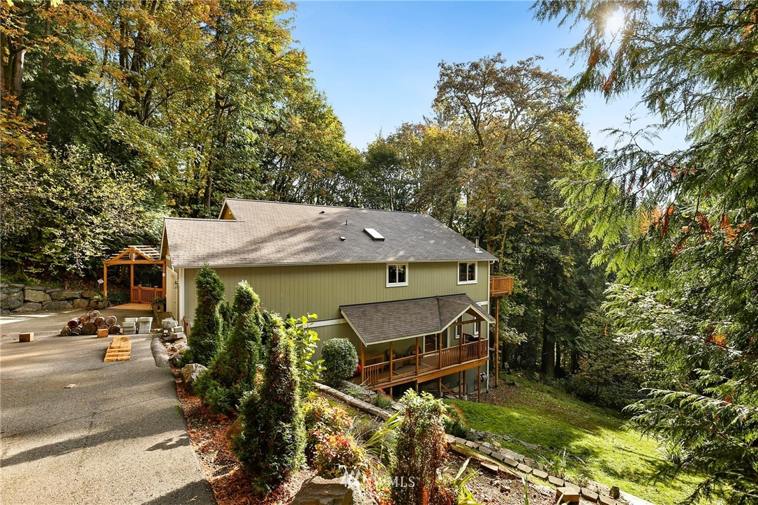 Forest retreat awaits! Main level guest bdrm & master suite w/attached 5pc bath; Family rm w/vaulted ceilings & wd burning fireplace w/french doors to view deck #1. Kitchen w/hickory cabinets, walk in pantry, new flrs & stainless appliances. Lower level great room is rough plumbed for wet bar, family room, bedroom #3, full bath & studio!  2nd deck, HUGE storage space under home, NEW furnace + A/C!