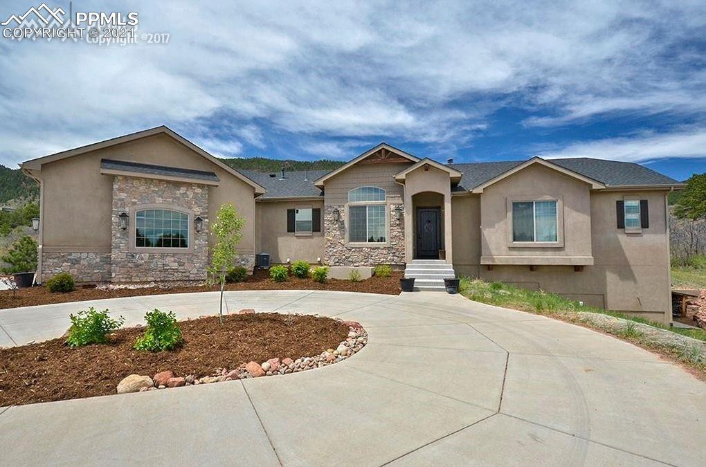 This home is in the perfect location if you want to feel like your worlds away but only minutes from I-25. Being close to I-25 puts you less than an hour to Denver and approximately 30 minutes to downtown Colorado Springs. Featuring 5 bedrooms, 2 on the main level, including the master, 5 bathrooms an office on the main level, and a huge 4 car garage that is fully finished and heated!!! The gourmet kitchen is loaded! and offers an amazing large granite island , gas cook top , double ovens , stainless steel high end appliances and a large pantry.   The kitchen is open to the living room with plenty of natural light shining through. The large main level master bedroom is like a retreat all of its own with a beautiful 5 piece bathroom and a large walk-in closet. There are 2 additional junior suites with their own private bathrooms. All of the bathrooms offer granite counter tops. The main. level office walks out on a wonderful deck with Mt. Herman in your backyard! Great main level living includes the laundry room. You will enjoy the open floor plan with large family areas that are great for entertaining or family gatherings. The family room downstairs has a granite counter top wet bar! There are 3 more bedrooms in the basement and plenty of storage.    The lot is amazing with the perfect balance of over 2.5 acres of trees and meadows. You will love the elevated views looking over Monument in the front and looking at the mountains in the back.  This is Colorado living at its finest.