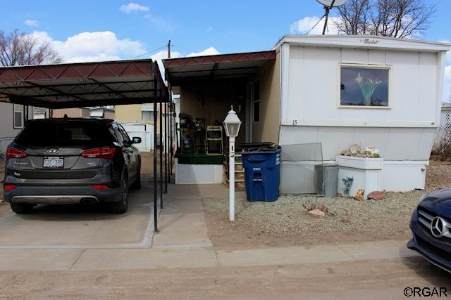 Must see home in the Rocky Mountain Mobile Home Community!  You will be pleasantly surprised with all the thoughtful upgrades to the recently upgraded kitchen... from the pull out shelving and custom spice rack to the big pantry in the kitchen. Tons of natural light in the kitchen and roomy living area which provides multiple options for furniture placement. Covered parking and a covered front porch entry will add to your enjoyment of this home. Back porch area has been enclosed to give you a large laundry area and even more storage. Currently 2 storage sheds on the lot provide additional storage for your outdoor equipment.  This one is ready for you to add your personal touches to the lot and home.