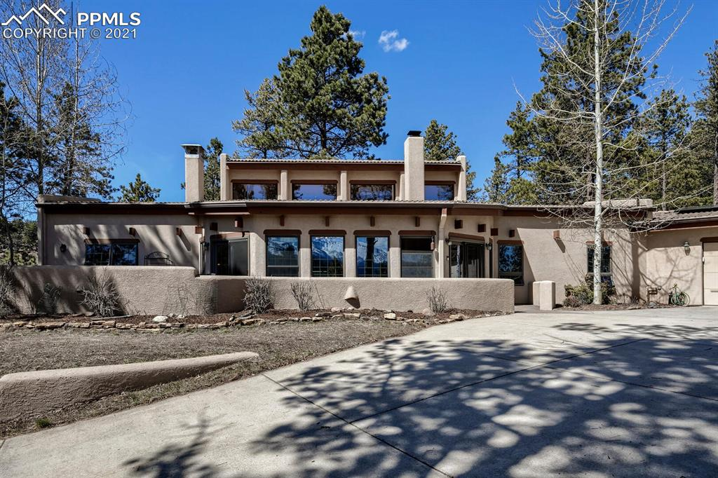 Killer Pikes Peak views, surrounded by trees and wildlife, yet walking distance to many conveniences and minutes to everything Woodland Park has to offer. Huge 4 car garage plus very private separate office / workshop area is perfect working at home, home schooling, or many hobbies. All on one level, and wide open floor plan with views out of almost every window. You'll never tire of the amazing mountain vistas from the private front patio. Utility bill friendly with solar electricity, plus radiant hot water heat and kiva type gas fireplace. Nicely updated kitchen with granite countertops, farmhouse sink, new dishwasher, refrigerator, stove and space saving drawer type microwave. Even has a boules court on the side of the house!