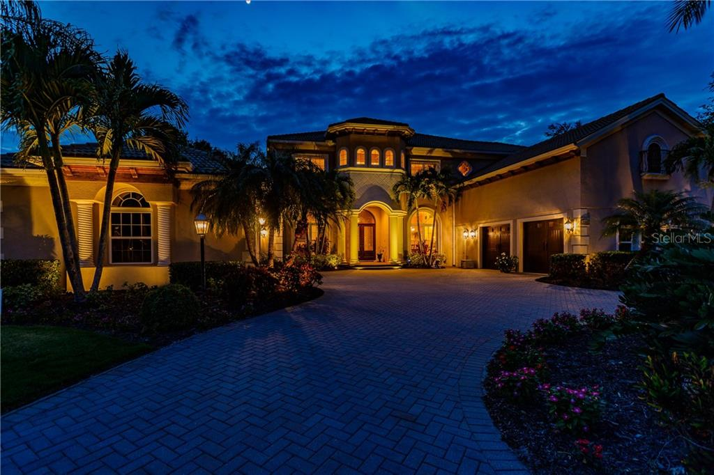 Deal fell through and back on the market. Celebrate life's success with your family and friends in this stunning estate within the highly sought-after Lakewood Ranch Country Club. As one of the largest homes in Lakewood Ranch, this 7,377 sq/ft residence has it all; with 5-bedrooms, 4-full baths, 2-half baths, 4-car garage, an office, den, game-room, and fully equipped movie theater. Located in Highfield, an exclusive enclave of luxury properties within the Country Club, the house sits on a private waterfront lot of .61 acres. As you make your way past the picturesque Arnold Palmer golf courses within the gated community, you're greeted by a circular driveway, lush tropical landscaping, and stunning curb appeal. Upon entering you're immediately struck by the luxurious finishes, attention to detail, and quality workmanship of this home, custom built in just 2007. Your family members will each have their own space to flourish, and your guests will enjoy certain privacy, but everyone will surely gather in the inviting and open living areas that make this home special. Occasions and entertaining are anchored by a gourmet kitchen featuring two walk-in pantries, center island w/prep sink, two-toned custom cabinets w/soft close drawers, granite countertops, stainless steel appliances, 6-burner range w/skillet, separate ice machine, elevated dishwasher, 3-ovens, microwave, warming drawer, huge side-by-side refrigerator & freezer, and a separate wet bar w/wine refrigerator. The master suite and bath are elegantly designed of considerable scale, showcasing a raised sitting area, a dressing area, dual walk-in closets w/custom built-ins, dual vanities & make-up counter, water closet w/bidet, and a raised jacuzzi tub. All 5-bedrooms are sized generously and have walk-in closets equipped with built-ins. The ample two and a half story floor plan offers a state-of-the-art movie theater, 4-wet bars, a huge game room w/billiard table adjoined by a large balcony overlooking the pool an