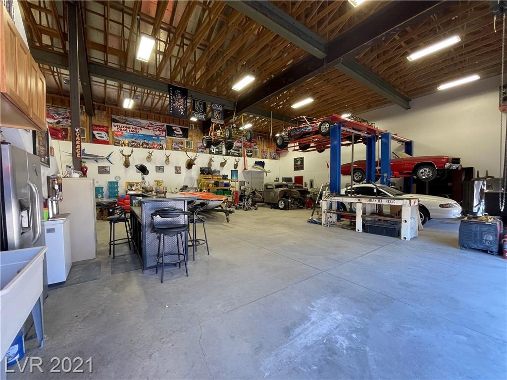 5000 sqft shop on almost an acre in Las Vegas w/ NO HOA... oh & did I mention, it comes with a house! This rare find features a single story home that measures almost 3600 sqft (includes permitted addition), 5 beds+den, 3 full baths, chef's dream kitchen, brick & wood floors throughout that brings so much character, formal dining area, upgraded security windows, ceiling fans in every room, extra large laundry area w/ a ton of cabinets & room for 2 refrigerators, AMAZING renovated master bath, full length covered patio in the back, artificial turf for easy maintenance, 2 RV gates, 2 car garage attached to the home, 1200 sqft garage detached from the home, & a 5000 sqft garage/RV Garage that is cooled w/ 3 swamp coolers & High Density Freezer Wall insulation on the back wall keeping it nice & cool. This sweet shop has a full bath, a urinal, a 26X50 loft, a possible 1600 sqft 2nd level room just needs floor/drywall, 2 Bendpak lifts, & a 11X20 loft in the Dbl RV garage w/ full RV hookups!