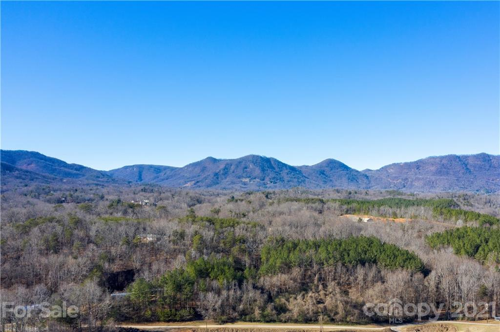 This 20+ acre Tract is located off Hunting Country Road and is Many Levels. This tract affords the owner peace of mind as it adjoins Cotton Patch of NC which is  250 acres of protected undeveloped land, protected in perpetuity by conservation easement. This Tract may be kept as one Tract or sub-divided into 2 Tracts as per the current survey. Both building sites have terrific mountain views and share the driveway. The water and electric to both building sites is already installed underground as is a phone line. You will not find more bucolic privacy with better views this close to town anywhere. Truly a one of a kind location with a WOW factor. 