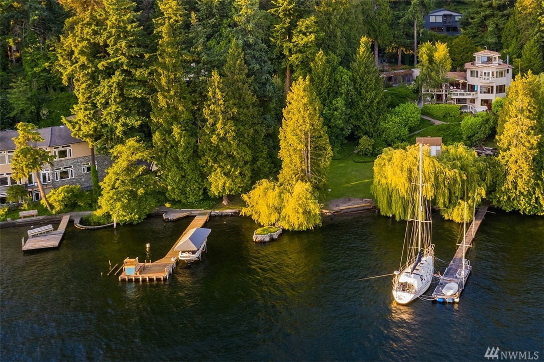240' of West-facing Lake WA waterfront cradled by Mt. Rainier, the Olympics & the gentle lapping of the waves. Over 1 acre of park-like grounds encourage nature to converge in a single joyful harmony from the sway of the willows, ripples on the water & pageantry of the eagles in flight. Inside, the architecture frames the views & charms all who enter w/ sunken fire-pit, lake view crow's nest & private MIL apt. The ultimate in waterfront living w/ 2 docks, 2 slips, cabana & sub-dividable acreage.