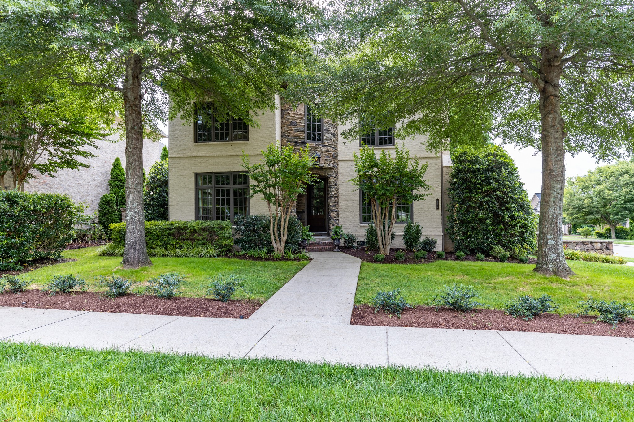 A beautiful corner lot, house nestled in the trees! It was the model home, with many upgrades.  Rooms are spacious, 2 bedrooms on main floor, one is the master. A great kitchen with a gathering room w/fireplace.  Fireplace in den with built in TV.  New windows on the front and new rock.  New painting throughout.   2 bedrooms up, rec room & library/office with built-ins.  Professionally landscaped! HOA includes a great pool, playground & walking trails. A must to see!