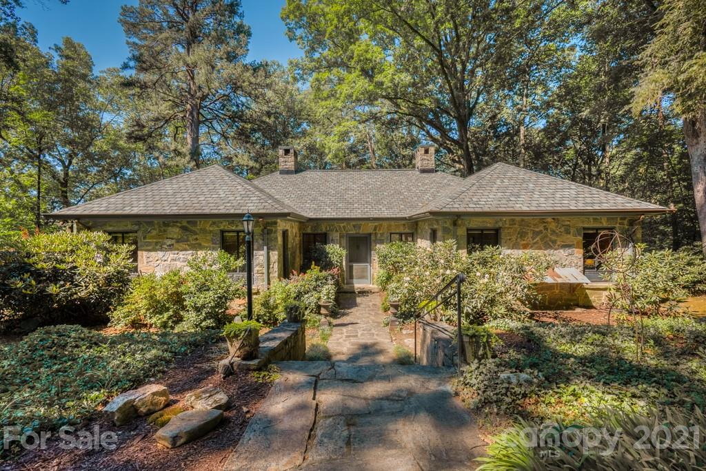 Delightful vintage charmer in Tryon's coveted Gillette Woods neighborhood. This circa 1929 stone home features 3 en-suite bedrooms and alluring period details, such as the stone fireplace with carved wooden mantle by the famed Tryon Toy Makers, solid wood floors and paneled walls, and original iron framed windows. The home sits elevated on a large wooded 5.2 acre parcel for ample privacy. The terraced landscapes behind the home include a winding trail down to the creek below. Seasonal mountain views, with year around possibilities. Brand new roof. Cozy and quaint, this home is well-suited for those seeking a unique, smaller, and older home, and those who appreciate the bygone character of vintage homes. Due to the age some updating may be required/desired. Don't let this gem get away, book your showing today! MULTIPLE OFFER SITUATION. HIGHEST AND BEST BY 5PM SUNDAY, JUNE 20.