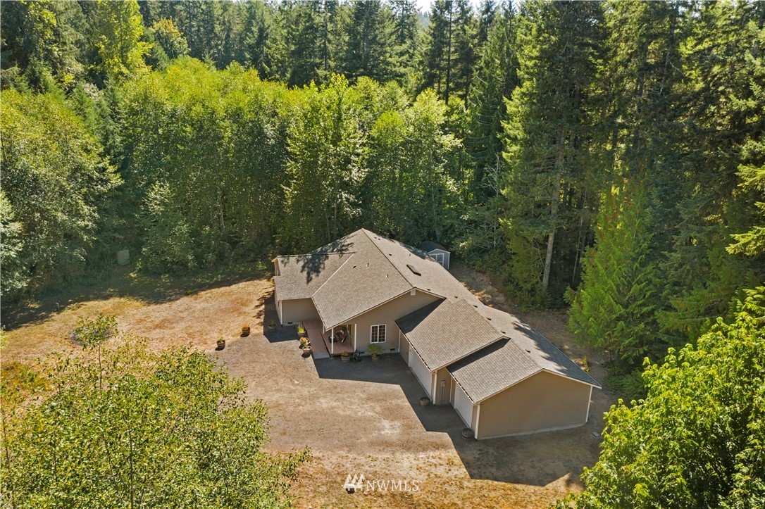 Ah... the total privacy and serenity of your forested acreage near Lake Tahuya!  Plenty of room to spread out in this mint condition 2006 built rambler featuring 4 spacious bedrooms, 3 car garage, RV parking with electrical hook up, and accessible entry, great room, primary bedroom & bath.  2320 total square feet in a terrific layout w/ formal & informal dining, a spacious great room & vaulted ceilings, double doors leading to the primary suite all w/ hardwood floors, and a separate hallway off the foyer to the 3 additional bedrooms/bath.  Convenient water closet & utility sink just inside from the garage.  High quality pellet stove keeps the house cozy.  New roof, interior paint, & carpet.  Loads of sun in the yard, easy drive to town.