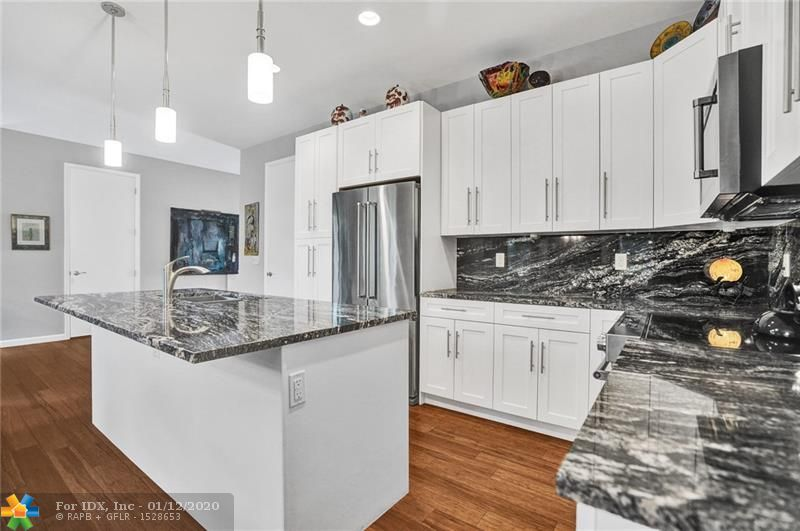 Live the life in this unique contemporary boutique community in downtown Oakland Park. This custom community of 6 townhomes were built in 2018. This one is a corner end unit with a large private fenced in yard, next to guest parking and across from the community pool. Features include an open living, dining & kitchen area, hi volume ceilings & wood floors throughout the home. Custom lighting, ceiling fans, & window treatments with impact windows & doors & generous size bedrooms.  The living area leads out to the expansive tropical private yard & patio area with a gate to access the sidewalks and streets of downtown Oakland Park. Steps away from Library, City Hall, Post office, Funky Buddha, & all the excitement Oakland Park has to offer. Exclude DR chandelier, sculpture & potted plants
