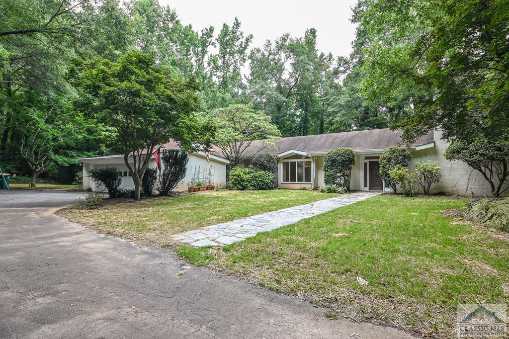 What  a great mid century ranch with room for everyone.  The house boasts 3373 sq.ft. per the Clarke County Tax Assessor and about 1.4 acres of woods and privacy.  You can imagine all the wild life, deer,  and birds for you to observe.  This house has exceptional living areas which include a very large living room with a fire place,  built in shelves and tons of windows,  a keeping room adjacent to the kitchen and an eating area that doubles as a  sunroom (it is all windows)!  You can relax and enjoy the privacy while sipping your  cup of coffee and reading the paper or your favorite book. The interior and exterior space is really amazing.  Adjacent to the keeping room is a large screened porch overlooking the wooded yard.  Hidden in the lush foliage are two little ponds that would be perfect for a few fish.  The screened porch flows into a second sunroom which has a large  hot tub...these  fun areas connect to the master bedroom and bath.  On the back side of the porch/sunroom is a lovely brick patio which also overlooks the spacious yard.   In addition to all of this  great indoor and outdoor space is a formal dining room, three more bedrooms, a huge laundry room,  a hall bath and  guest bath.  All of the bedrooms have lots of closets, natural light and tons of windows. A carpet allowance is available with an acceptable offer.   Don't miss taking a look at this intriguing home.