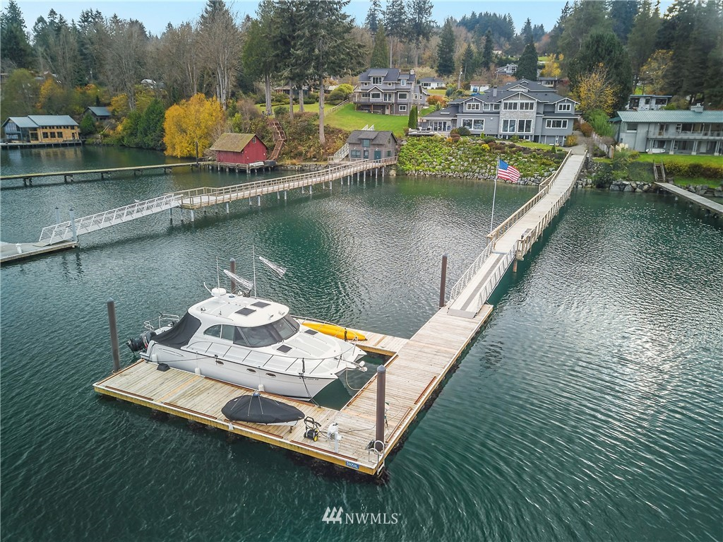 Waterfront resort style living with your own 4 slip deep water dock on Eagle Harbor.  Just a short commute to Seattle by private boat from your own dock or short drive into Winslow to catch the Bainbridge Ferry.  The main house has 4 en suite bedrooms with views, private office space, living and dining areas, indoor pool, and daylight basement with plenty of storage.  The Recreation Center has a 13 seat home theatre, game room, gym, 1/2 court basketball court, bathrooms, and meeting space.  This space could also be converted to a home business, car collection, climbing gym and more.  The sunny and beautifully landscaped .98 acre property is planted with edibles (asparagus, garlic, plum, potatoes+) and a gorgeous display of flowering plants