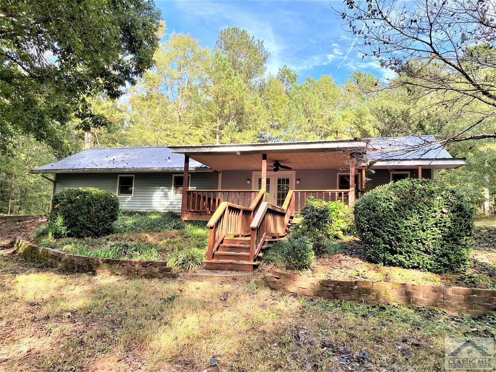 Unbelievable opportunity to own 5 private acres in Oconee County!  Gated long driveway brings you to this darling location with a metal roofed home, surrounded by woods!  Front porch is perfect for rocking and chilling.  Enter large great room open to kitchen.  Continue to left to huge master bedroom with attached bathroom.  All floors in living area are tiled.  Perfect for pets.  Other side of the home has a bedroom and bathroom and a laundry room with outdoor entrance and extra space for projects!   Out back is a large open 3-sided garage/shed,  probably big enough for 2 large pick-up trucks and about 24' of shelves to store lots of tools and equipment and your workshop.  Back of shed has new hardiplank and new flashing.  Another outbuilding is a small barn, good for chicken coop or storage.  Best of all, you are surrounded by trees.  Not another house in sight!   Great spot to add your own touches and maybe enlarge the house to fit your needs.  Award-winning school system!  HVAC 2 years old, new hot water heater, metal 26-gauge roof installed about 5 years ago.  Bored well and septic. High-speed internet available. Great opportunity to make your dreams come true!