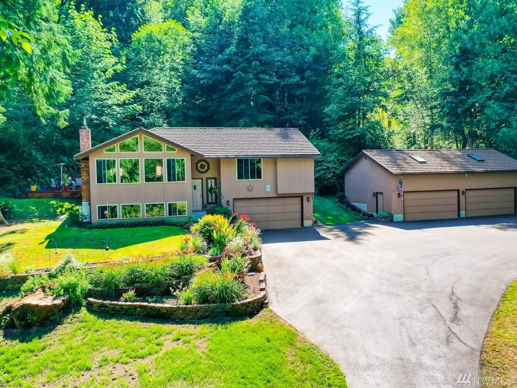 Beautifully unique 3+ acre estate on park-like grounds in Enumclaw's desirable Y Bar S! This well-maintained, single owner home includes a kitchen update and vaulted great room with a light-filled wall of windows displaying incredible views of Bass Lake and the foothills. Propane fireplace and full bar downstairs are perfect for any size gathering and heat pump keeps you cool during these hot summer days and nights! Detached, 4-car, heated garage is perfect for the enthusiast of any kind.