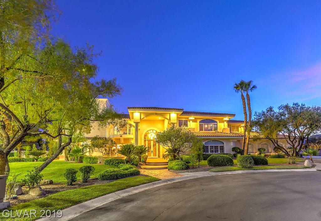 Entertainer's Dream!! Located near DownTown Summerlin at the end of a cul-de-sac, this 6 bedroom, 5 bath gem is one of 2 homes in the guard gated community that sits on a double lot with over 7400 sqft of living space, a private tennis court, & a large 8 car custom garage*Resort Style Pool/Spa with a grotto, waterfalls, & waterslide! Game Room*Gym*Rooftop Deck with a panoramic view which includes The Strip, Red Rock mountains, & the entire city!