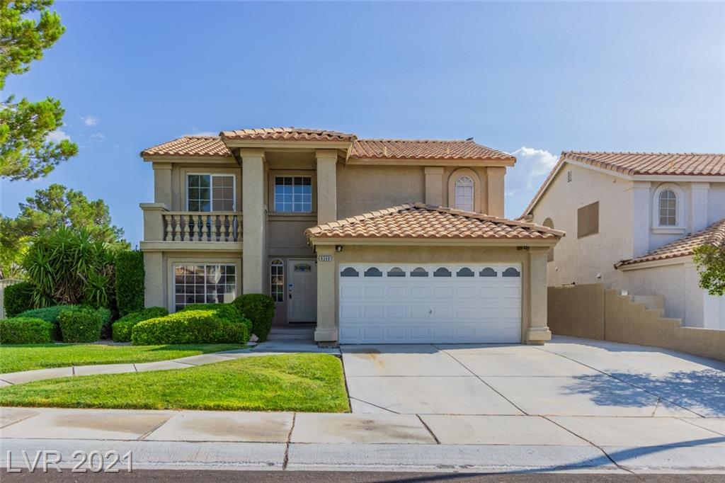 This Las Vegas two-story home offers an in-ground pool, granite countertops, and a two-car garage.