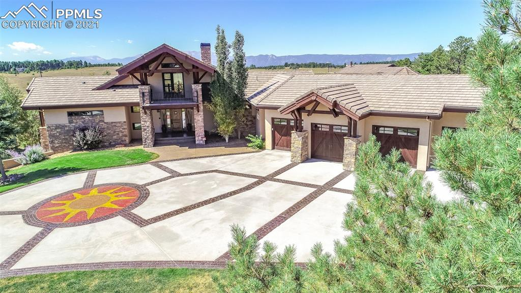 Spectacular home w/unobstructed views of front range & Pikes Peak. Special features include a recently added main level, in-law suite w/1,232 sq. ft. w/ living room, kitchen, laundry & junior master suite. Below this suite, there is a 700 sq. ft workshop w/garage door. The focal point of the home is the great room w/wide-plank hardwood floors, stone fireplace w/gas logs, wall of glass & 2-story peaked ceiling w/wood beams & chandelier. Gourmet kitchen w/beech wood cabinets, slab granite counters, pot filler, Wolf 6-burner gas range w/griddle, double Wolf ovens, Sub-Zero fridge, central vac crumb catcher & counter seating. Kitchen opens to dining room w/fireplace & hearth room w/fireplace. Kitchen, dining & hearth rooms have wide-plank hardwood floors & open to an amazing Trex deck w/approximately 1,584 square feet. Deck is partially covered & offers a gas line, wrought-iron railings, stone columns & audio speakers. Off the hearth room there is an indoor/outdoor room w/stackable windows, heated tile floor & wine bar area. The main level Master features a peaked ceiling w/fan, custom plantation shutters & a see-thru fireplace to the luxurious bath. The 5-piece master bath has heated tiled floors, slab granite counters, beech wood cabinetry, jetted tub, steam shower w/3 shower heads to include a rain head & a walk-in closet w/washer & dryer hookup. Main level office w/French doors & wood floors. Walk-out lower level features a second great room w/wet bar, theater area w/tiered seating, fireplace & exercise/ game area. Upper level loft (or 2nd office) has overlook to main level great room. Alder woodwork & doors thru-out. Whole house intercom & sound system. 5 fireplaces. A/C on main level. Radiant heat in master bath, in-law suite & lower level. Forced air heat elsewhere. Extensive landscaping. Huge flagstone patio in back w/inviting fire pit. This is a premier home w/a great setting & forever views. 4-car garage w/epoxy floor. Guaranteed to impress.