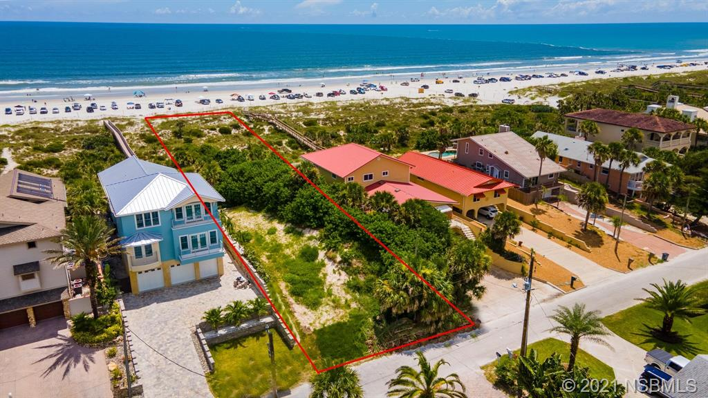 Incredible opportunity to build your dream home on this beautiful, direct ocean-front lot, located in one of the best spots in New Smyrna Beach.  High elevation offers panoramic Atlantic views and protective rolling dunes.  Imagine endless ocean breezes and spectacular sunrises, steps from the sand on coveted North Beach.  Catch the east coast's best waves and live the endless summer you've always dreamed of.  Just past NSB's last beach exit and equidistant from the serenity of the Smyrna Dunes Park and the festive shops and restaurants of Flagler Ave, this location truly has it all.  Make it yours today.