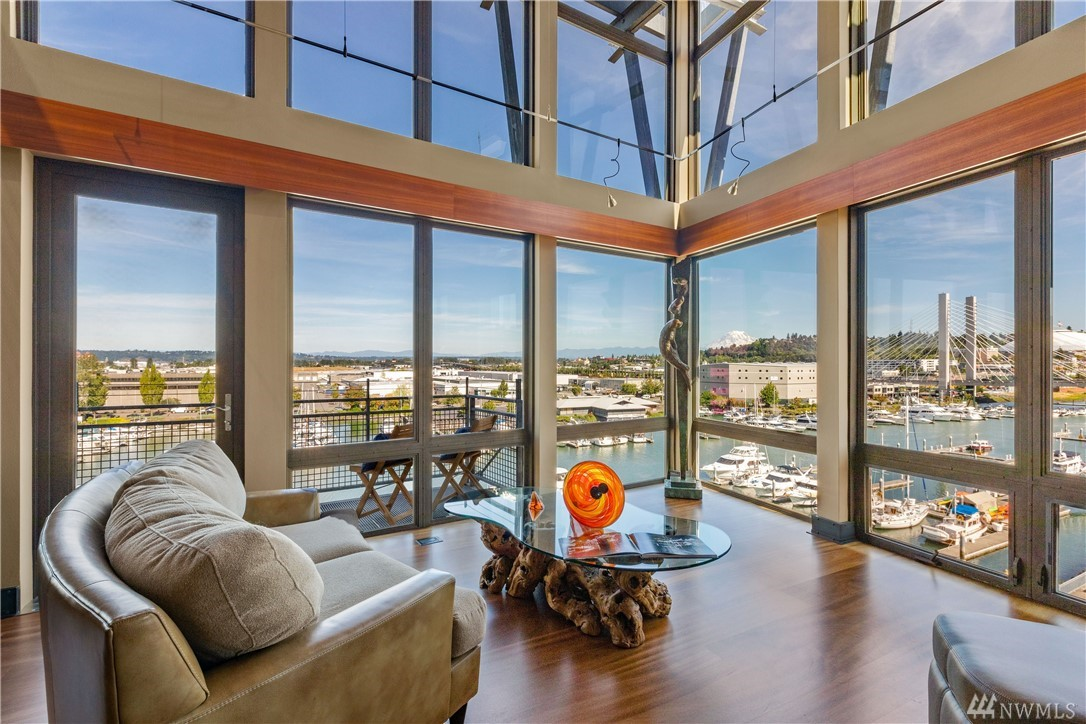 Corner penthouse boasts a wall of glass presenting some of finest views in Tacoma & of Mt. Rainier w/miles of Cascade foothills. Stunning home has been comprehensively renovated w/chef's kitchen, glass counters and design finishes from local artisans inspired by adjacent Museum of Glass. Enjoy an active lifestyle while capturing the maritime energy of the Foss waterway. Main floor master catches the morning sun and upper loft has a custom designed bookcase that opens to reveal a Murphy bed.