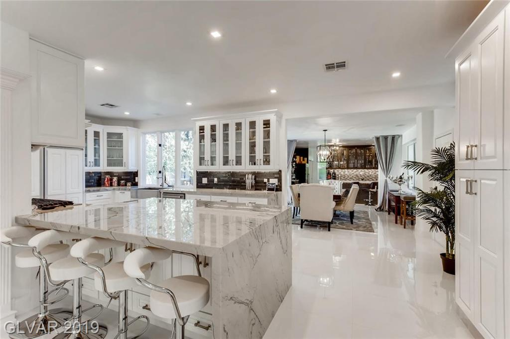 ADDITIONAL 644sqft in this completely remodeled smart home! 200K in upgrades.  New white porcelain tile t/o, fixtures, faucets, & paint! Kitchen has new marble countertops, cabinets, appliances, hardware, B/I wine fridge & ice maker  Living & Dining room open to the lovely backyard with putting green Master has balcony, 2 person jetted tub.  All 5 bathrooms completely remodeled w/marble, state of the art showers. 2 fireplaces with stacked stone.