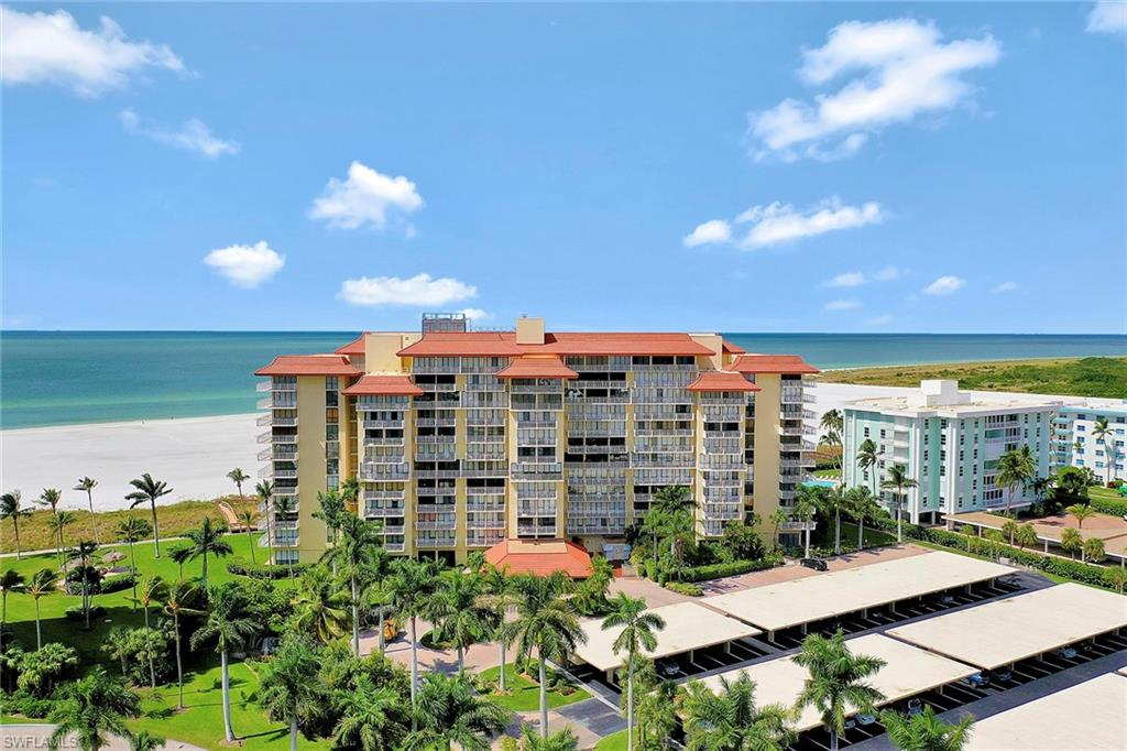 Beautifully updated light and bright nicely furnished beachfront condo offering Island and partial Gulf views from your private balcony.  Kitchen comes with stainless appliances, plenty of cabinets and pantry. Gorgeous stone composite wood-like flooring throughout for easy maintenance. Electric updated in 2019. Spacious walk-in closet in master bedroom. Additional storage locker, trash chute, and common laundry facilities on every floor. Assigned covered carport space with extra storage. Amenities include a Social Room with Kitchen, Large heated Pool with grill area, Vehicle wash, Tiki Huts, and private beach access. Tradewinds is a low density updated building with secured lobby and on-site manager. Surrounded by lush tropical landscaping. Owner has paid all assessments for installation of impact glass windows and doors. Close to restaurants and shops. Great investment property. This unit is a must see. Start living the island life-style you've been waiting for.